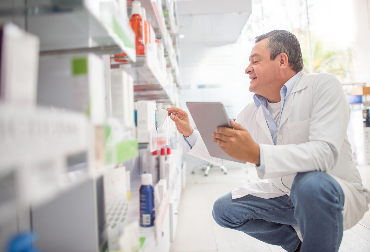 Happy pharmacist doing the inventory at a drugstore using a tablet computer