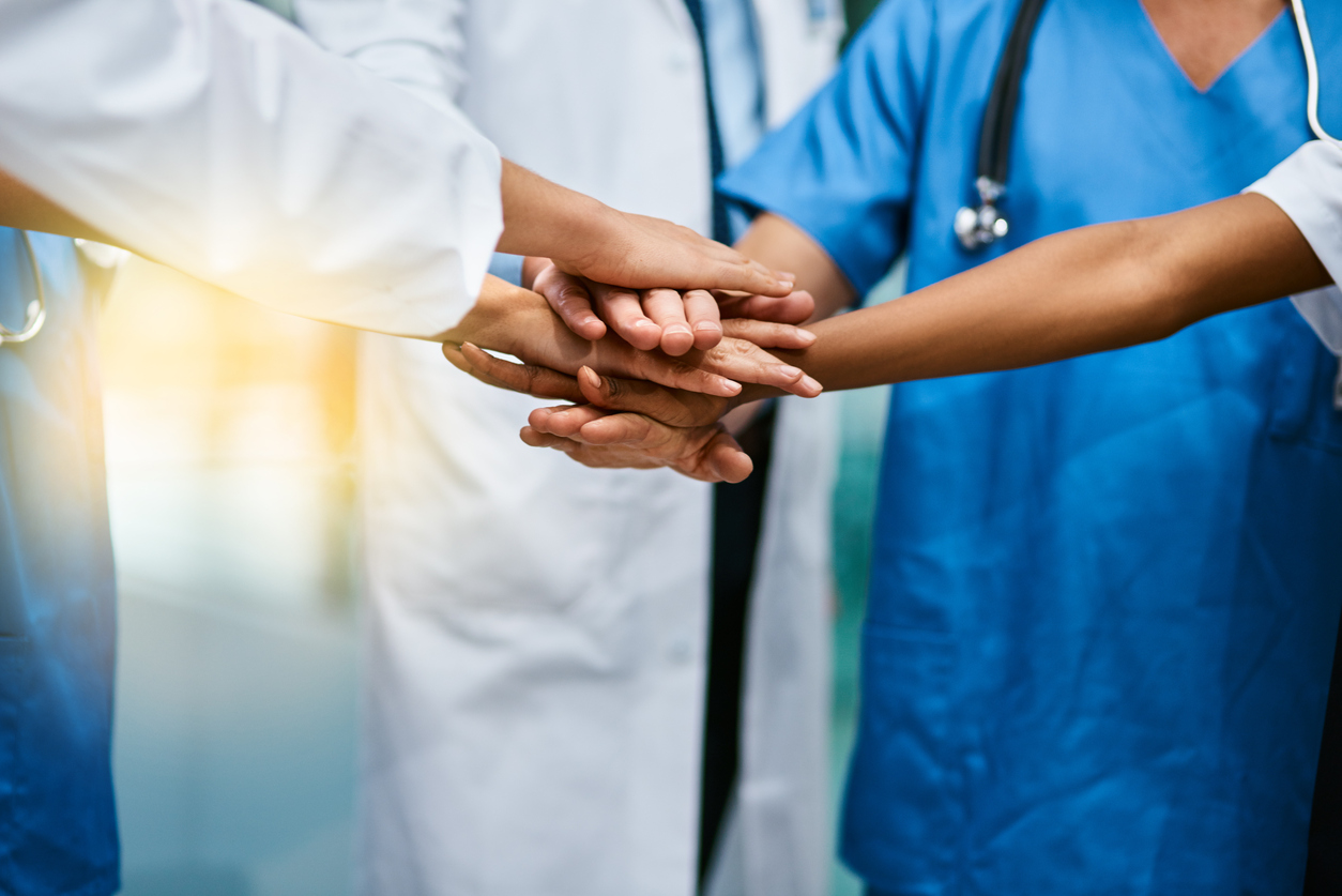 group of doctors with hands in middle as concept of teamwork