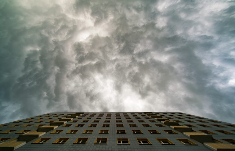 Facade a building and a stormy sky. Severe weather planning concept