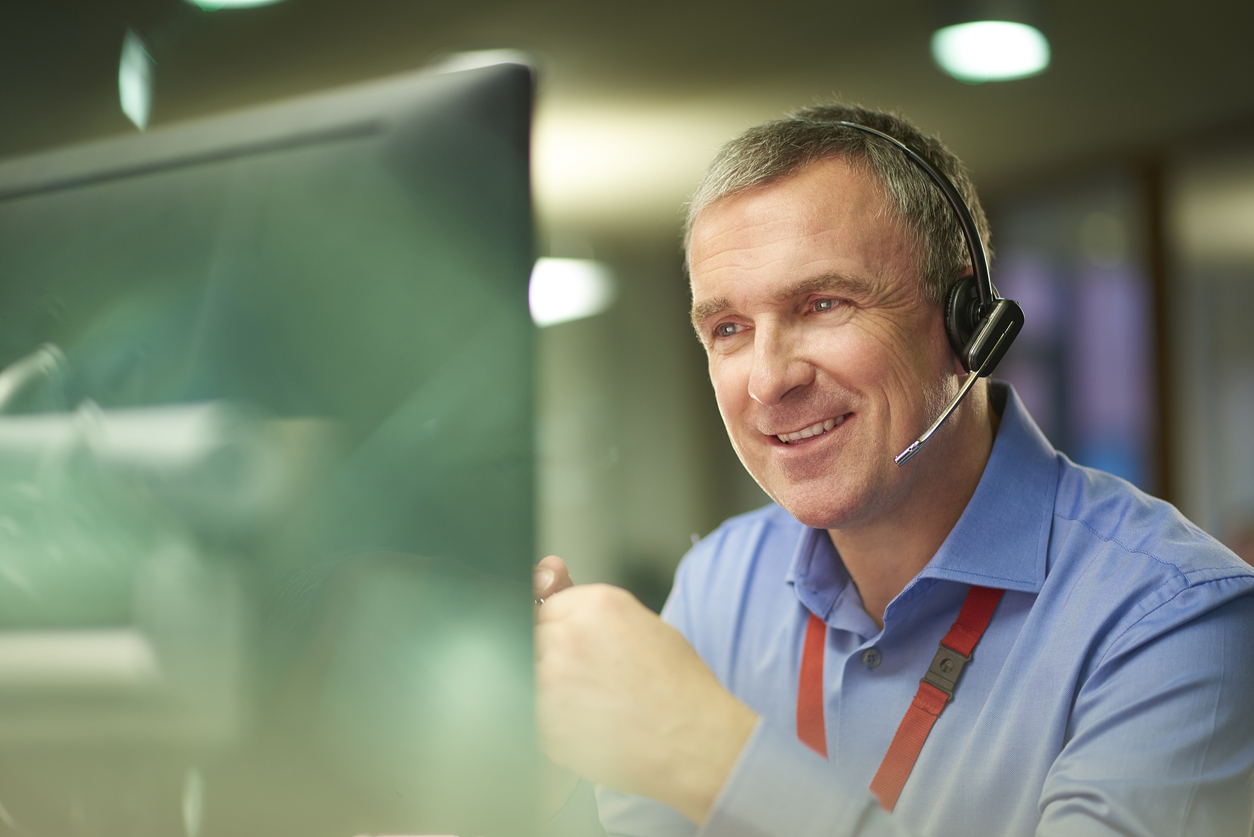 a call centre phone operative in his mid 40s chats on the phone at his desk . He is explaining something to the person on the phone in a friendly manner . behind him a defocussed office interior can be seen . This could be a call centre or an office worker chatting to a customer.