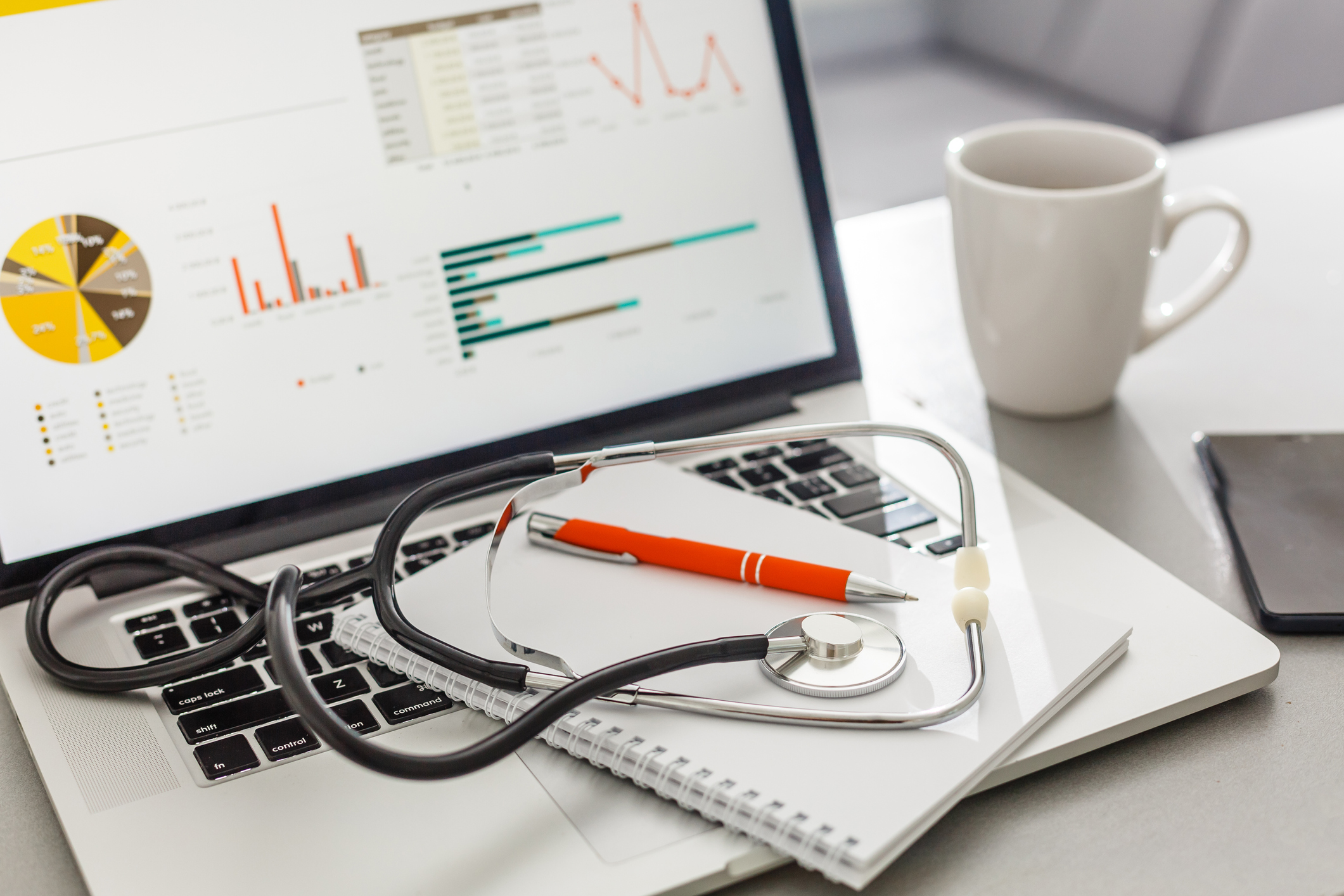 computer-monitor-with-keyboard-notebook-stethoscope-and-coffee-mug